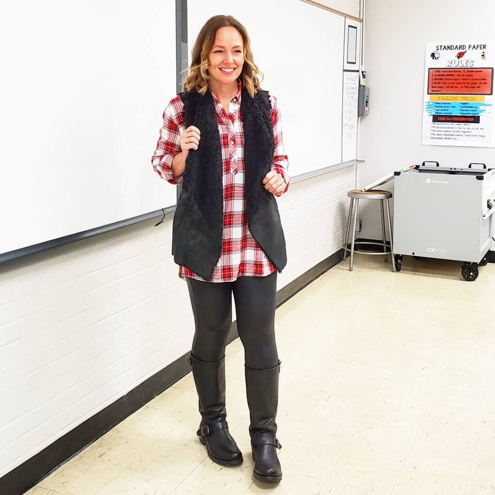 Casual holiday outfit idea with Christmas plaid shirt, shearling fur vest, faux leather leggings, and boots