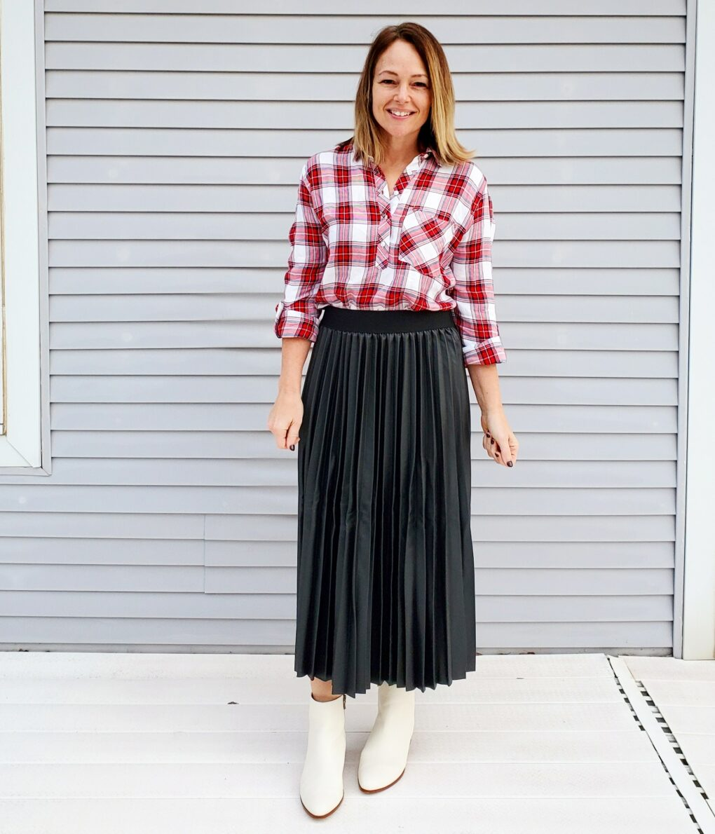 Casual holiday outfit idea with Christmas plaid shirt, faux leather pleated skirt, and white boots