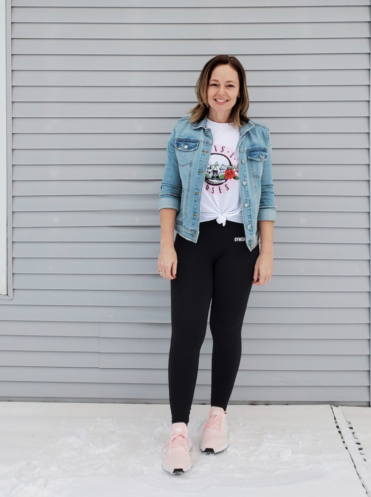 Casual weekend outfit featuring a Guns n Roses band tee, denim jacket, Gymshark leggings, and pink Adidas Originals sneakers