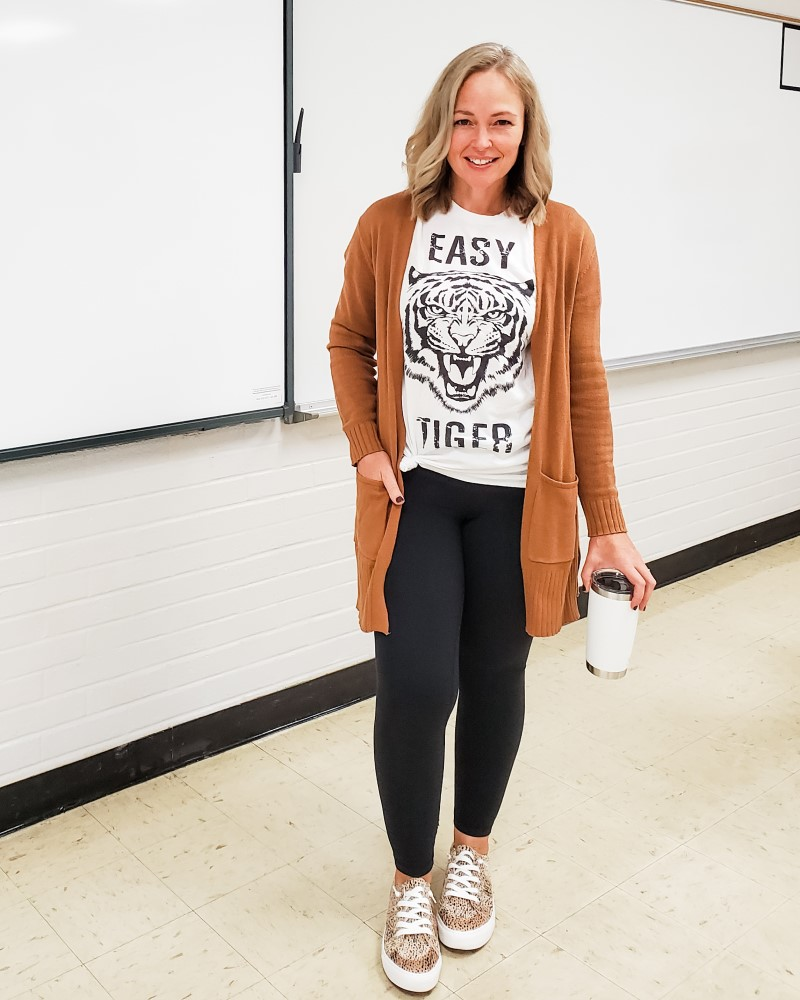 Casual teacher outfit featuring a graphic tiger tee, tan caramel long cardigan, black leggings, and leopard print sneakers