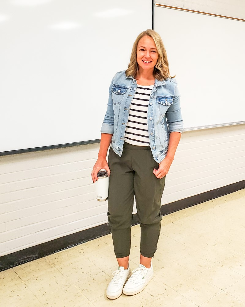 Teacher outfit featuring olive joggers, a striped top, a denim jacket, and sneakers