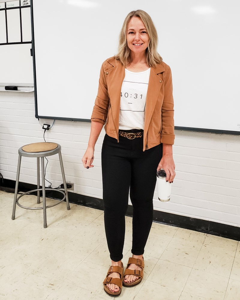 Casual teacher outfit featuring a tan knit moto jacket, graphic tee, leopard print belt, black jeans jeggings, and suede Birkenstock sandals