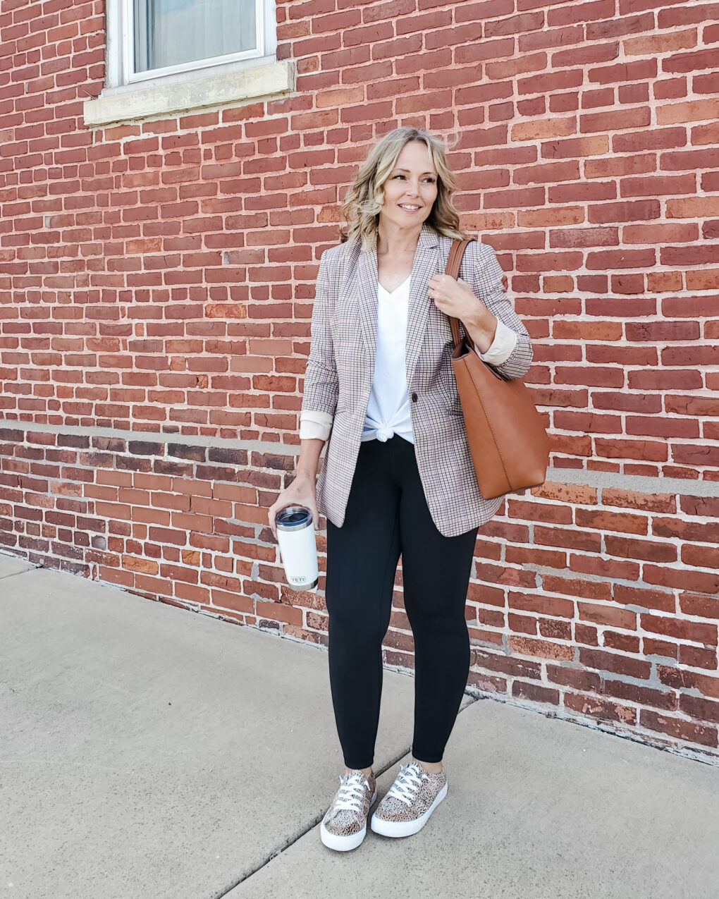 Teacher outfit with plaid blazer, white tee, black leggings, leopard print shoes, and a tan tote bag
