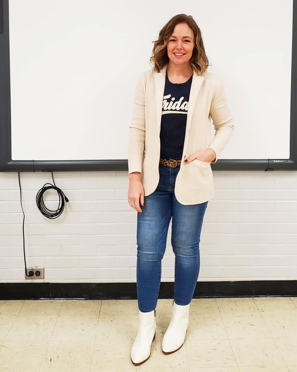 Casual teacher outfit with a white knit sweater blazer, graphic tee, jeans, white booties, and a leopard belt