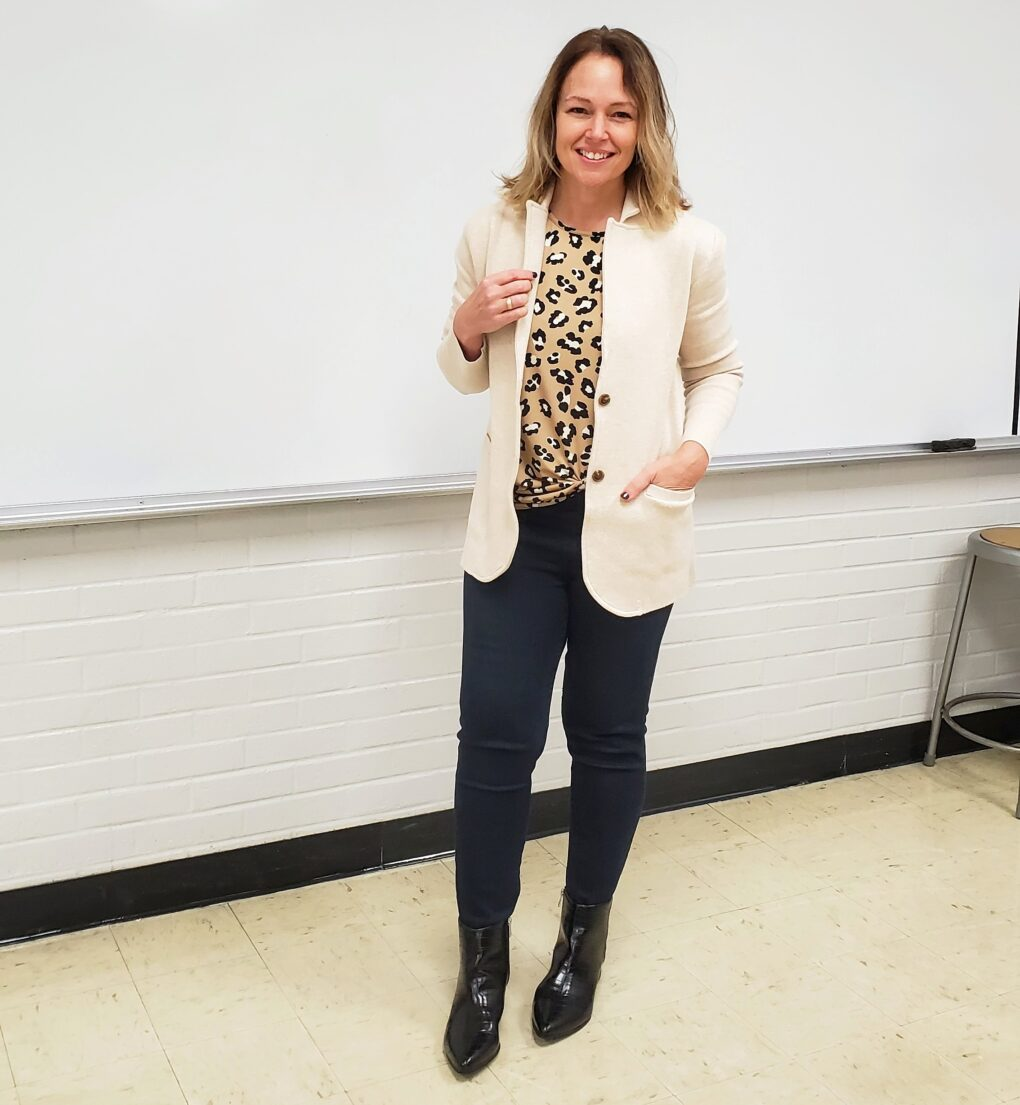 Teacher outfit with white knit blazer, leopard top, black pants, and black booties