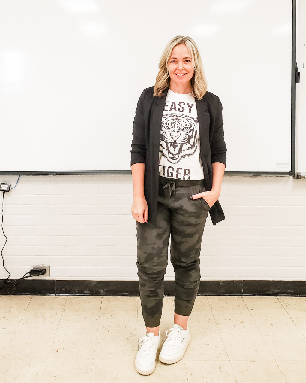 Casual teacher outfit with a black boyfriend knit blazer, graphic tee, camo joggers, and white sneakers