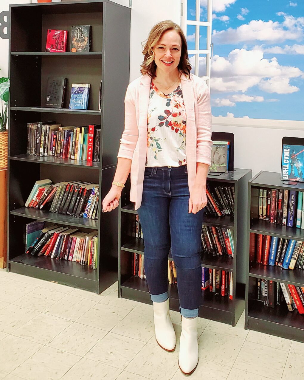 Teacher outfit with pink knit sweater blazer, dark jeans, white boots, and a floral print top