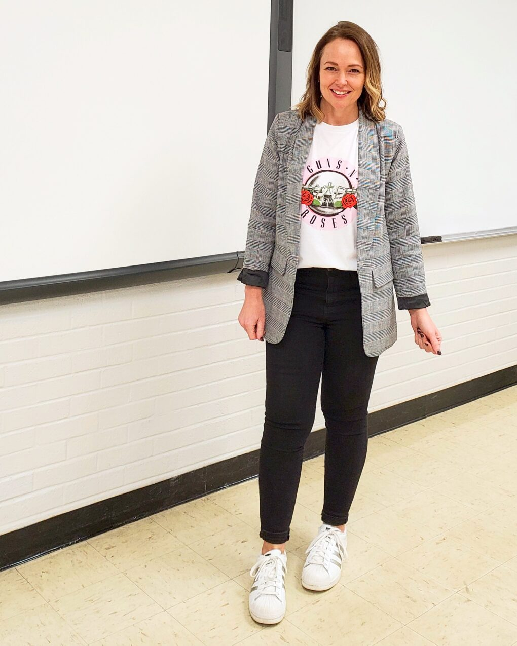 Teacher outfit with plaid blazer, rock band tee, black jeans, and white sneakers