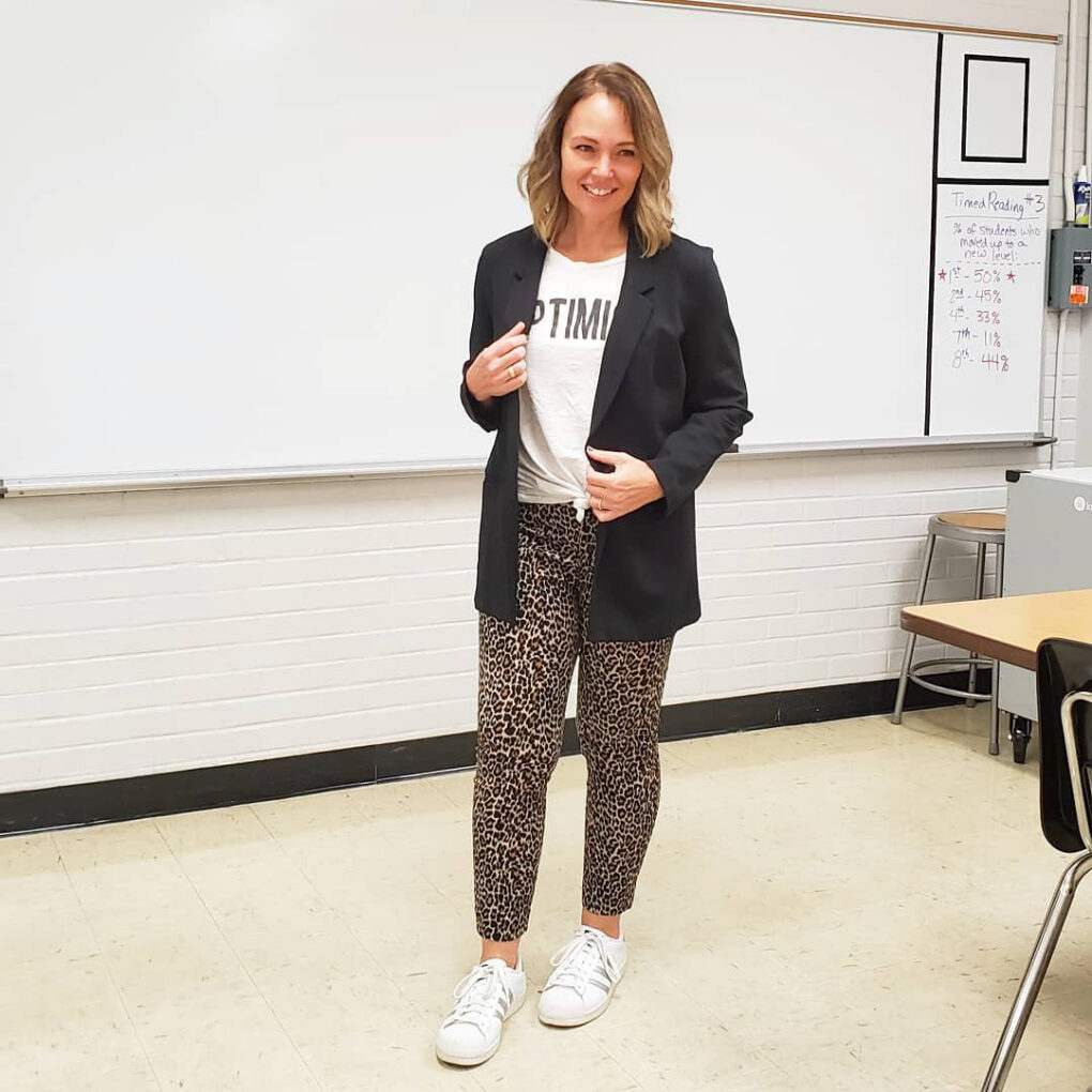 Teacher outfit with a slouchy knit blazer, graphic tee, leopard print pants, and white sneakers